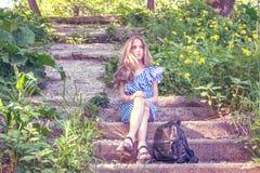年轻美丽的女孩坐台阶在有花的公园, 免版税库存照片