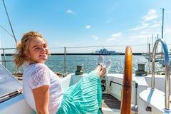 年轻美丽的女孩坐游艇在舵附近在海并且看在甲板的照相机 免版税库存图片