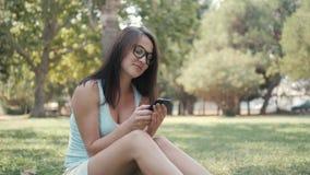 年轻美丽的女孩坐草坪在公园使用电话,网上购物概念 免版税库存照片