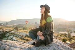 年轻美丽的女孩实践的瑜伽在一座山顶部在日出的卡帕多细亚 放松实践  图库摄影