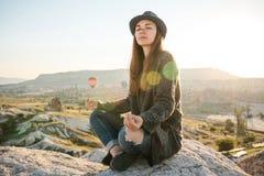 年轻美丽的女孩实践的瑜伽在一座山顶部在日出的卡帕多细亚 放松实践  免版税图库摄影