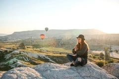 年轻美丽的女孩实践的瑜伽在一座山顶部在日出的卡帕多细亚 放松实践  免版税库存图片