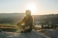 年轻美丽的女孩实践的瑜伽在一座山顶部在日出的卡帕多细亚 放松实践  库存照片