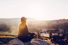 年轻美丽的女孩实践的瑜伽在日出的一座山顶部 放松实践  免版税库存图片