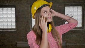 年轻美丽的女孩建造者在智能手机,观察,通信概念谈话 股票视频