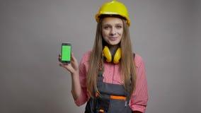 年轻美丽的女孩建造者显示她的智能手机色度屏幕,微笑,通信概念,灰色背景 影视素材