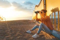 年轻美丽的女孩旅客坐海滩并且通过双筒望远镜看 旅行假日旅途概念 免版税图库摄影