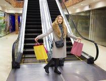 年轻美丽的女孩是愉快的反对一个自动扶梯的背景在与购物袋的一个购物中心 图库摄影