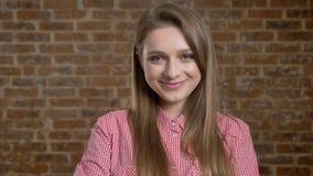 年轻美丽的女孩显示以后的姿态,调情的人,通信概念,砖背景 股票视频