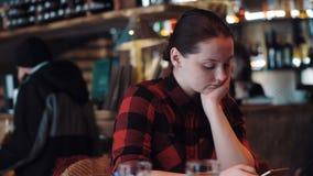 年轻美丽的女孩浏览电话的互联网在酒吧 股票视频