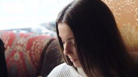 年轻美丽的女孩浏览电话的互联网在酒吧 影视素材