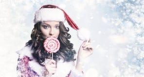 年轻美丽的女孩用在多雪的冬天背景的糖果 圣诞节和新年假日概念 免版税库存图片