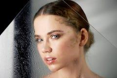 年轻美丽的女孩画象在演播室,有专业构成的 秀丽射击 在一块透明玻璃面前 免版税库存照片