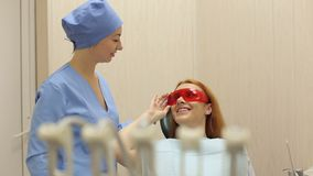 年轻美丽的女孩谈话与她的牙医在牙齿办公室 牙科 影视素材