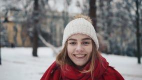 年轻美丽的女孩走在圣诞树附近的温暖的衣裳的 慢的行动 时髦的年轻人画象  股票录像