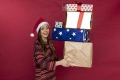 年轻美丽的女孩运载很多礼物 免版税库存照片
