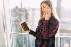 年轻美丽的女孩饮用的咖啡和谈话在电话,办公楼的一名妇女 库存图片