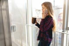 年轻美丽的女孩饮用的咖啡和谈话在电话,办公楼的一名妇女 库存照片
