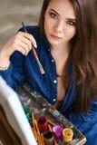 年轻美丽的女孩,认为一件新的艺术品的女性艺术家画家和准备做第一绘画的技巧 库存照片