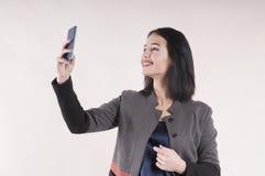 年轻美丽的女实业家画象快乐的电话微笑的括号演播室,做selfie 免版税库存图片