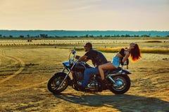 年轻美丽的妇女和人坐摩托车 免版税库存图片