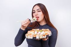 年轻美丽的妇女喜欢吃寿司,在白色的演播室射击 库存图片