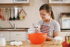 年轻美丽的妇女在厨房里烹调 免版税库存照片