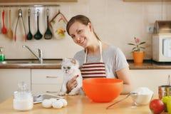 年轻美丽的妇女在厨房里烹调 库存图片