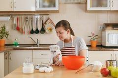 年轻美丽的妇女在厨房里烹调 免版税库存图片