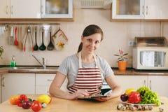 年轻美丽的妇女在厨房里烹调 库存照片