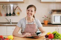 年轻美丽的妇女在厨房里烹调 免版税图库摄影