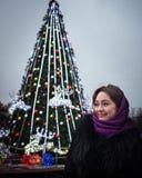 年轻美丽的妇女在圣诞节杉树的背景站立 免版税图库摄影