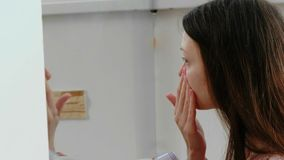 年轻美丽的妇女在她的在镜子前面的面孔上把奶油放 侧视图 股票视频