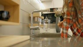 年轻美丽的妇女在家庭厨房里洗盘子,支持水槽 股票视频