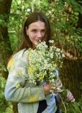 年轻美丽的妇女在有花束的o森林里站立 免版税图库摄影