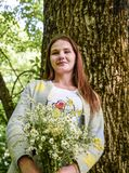 年轻美丽的妇女在有花束的o森林里站立 图库摄影