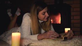 年轻美丽的妇女在毯子说谎通过壁炉和读书 股票录像