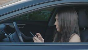 年轻美丽的妇女在汽车时使用一个智能手机,当坐 股票视频