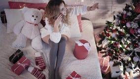 年轻美丽的妇女在电话坐与玩具熊的一张床在圣诞树附近并且谈话 顶视图 股票录像