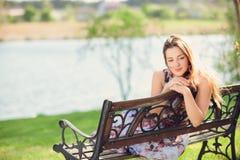 年轻美丽的妇女坐在公园俏丽的女孩的长凳在夏日自然的户外 可爱的女孩在公园坐是 库存照片