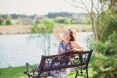 年轻美丽的妇女坐在公园俏丽的女孩的长凳在夏日自然的户外 可爱的女孩在公园坐是 库存图片