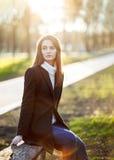年轻美丽的妇女坐在太阳光的一条长凳在日落 免版税库存图片