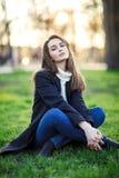 年轻美丽的妇女坐在太阳光的一棵草在日落 免版税库存图片