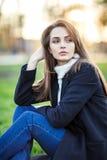 年轻美丽的妇女坐在太阳光的一棵草在日落 库存照片