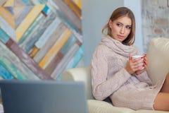 年轻美丽的妇女坐在白色砖墙背景的一个沙发与一杯咖啡 膝上型计算机,文件 图库摄影