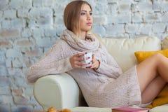 年轻美丽的妇女坐在白色砖墙背景的一个沙发与一杯咖啡 膝上型计算机,文件 免版税库存图片