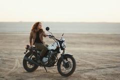 年轻美丽的妇女坐她的老咖啡馆竟赛者摩托车在沙漠在日落或日出 免版税库存照片