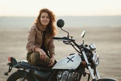 年轻美丽的妇女坐她的老咖啡馆竟赛者摩托车在沙漠在日落或日出 库存照片
