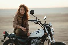 年轻美丽的妇女坐她的老咖啡馆竟赛者摩托车在沙漠在日落或日出 免版税图库摄影