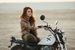年轻美丽的妇女坐她的老咖啡馆竟赛者摩托车在沙漠在日落或日出 免版税库存图片